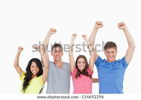 A smiling group as they celebrate with their hands raised in the air - stock photo