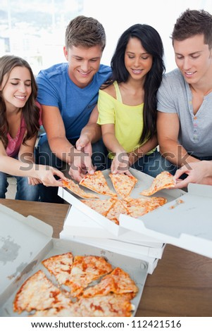A smiling group helping themselves to the pizza in front of them