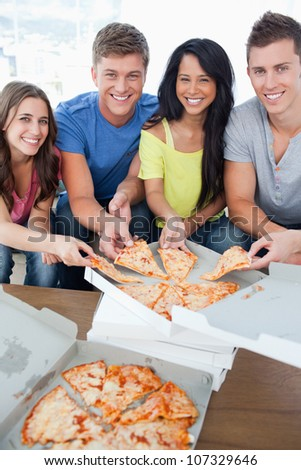 A smiling group of friends as they look into the camera and take some pizza - stock photo