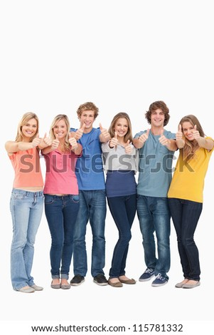 A smiling group of friends giving at thumbs up while looking at the camera - stock photo