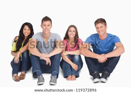 A smiling group of friends sitting beside each other on the ground with their hands on their legs