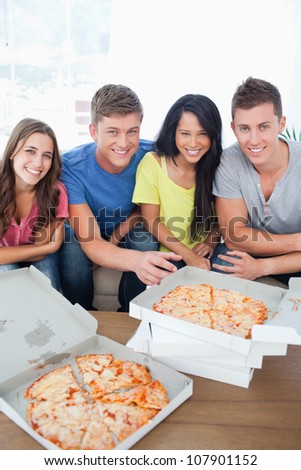A smiling group of people about to eat as they look at the camera