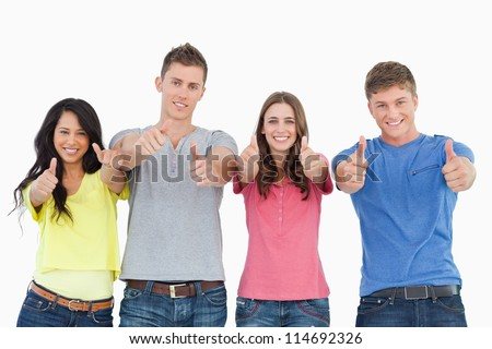 A smiling group of people stand beside each other looking at the camera as they all give thumbs up - stock photo
