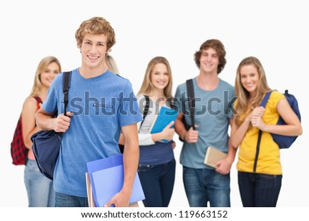 A smiling group of students all looking at the camera while one man stands in front of the rest of the group - stock photo