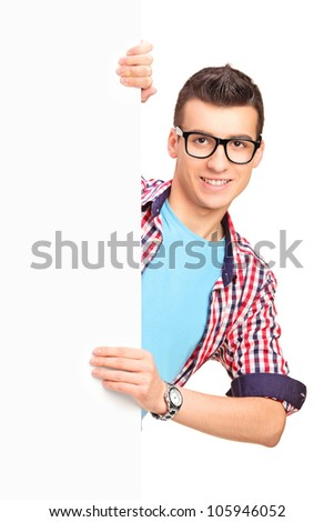 A smiling handsome male posing behind a white panel isolated against white background - stock photo