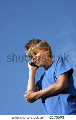 a smiling handsome 10-years old boy phoning with his cell phone, photographed in the summer sun with blue sky and tiny clouds in the background