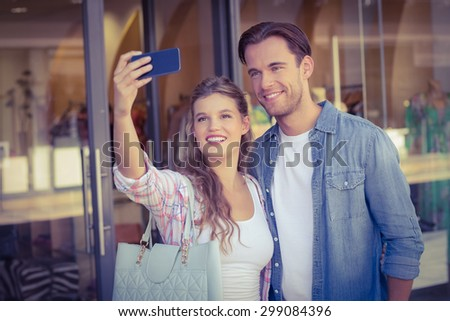 A smiling happy couple taking selfies at the mall - stock photo