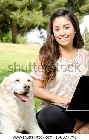 a smiling Hispanic woman sitting in the park with her dog and a computer. - stock photo