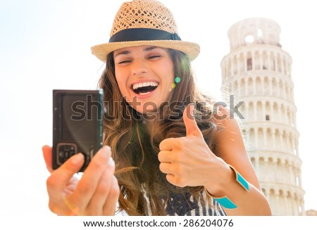 A smiling, laughing woman tourist is taking a selfie at the Leaning Tower of Pisa, giving a happy thumbs up. What a joy it is to travel! - stock photo