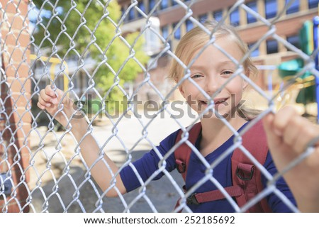 A smiling little girl at school playground - stock photo