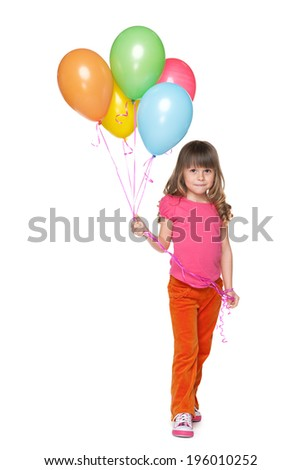 A smiling little girl holds balloons against the white background - stock photo