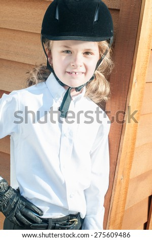 A smiling little girl in English riding attire leans against a shed.  She wears a black velvet helmet, leather riding gloves, white shirt, black jodhpurs and gold buckled belt.  - stock photo