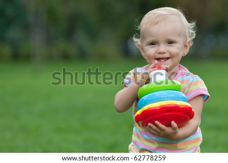 A smiling little girl is holding a toy pyramid in her hands while walking out in the park - stock photo