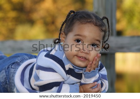 A smiling little girl laying on a bench resting on hand - stock photo