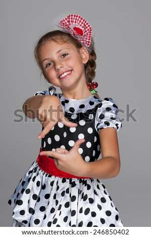 A smiling little girl makes a hands gesture against the gray background - stock photo