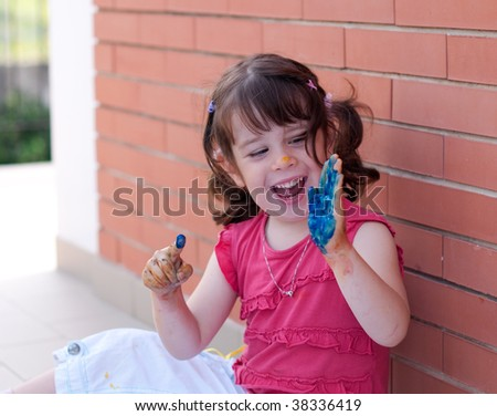 A smiling little girl painting blue her hand - stock photo