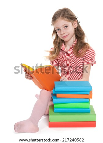 A smiling little girl sits on the floor near the pile of books and reads