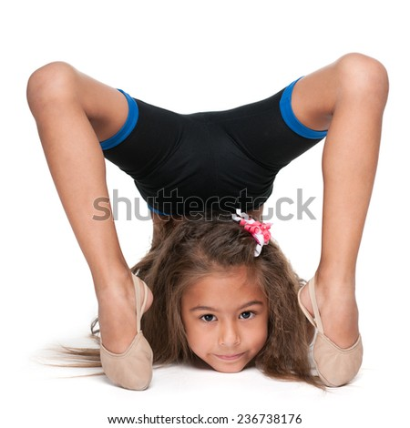 A smiling little gymnast does exercises against the white background - stock photo