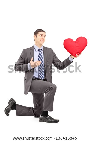 A smiling male in a suit kneeling with red heart isolated on white background - stock photo