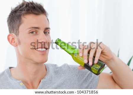 A smiling man as he holds some beer in his hand as he is about to drink - stock photo