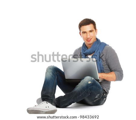 A smiling man working with a laptop on the floor, over white - stock photo