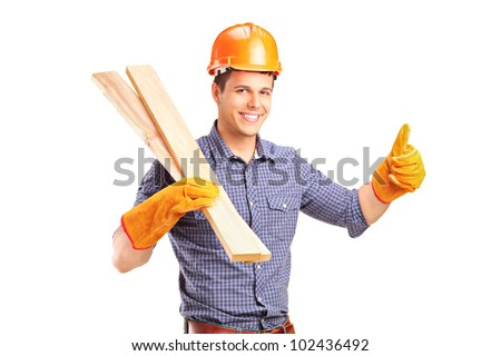 A smiling manual carpenter holding sills and giving thumb up isolated on white background - stock photo