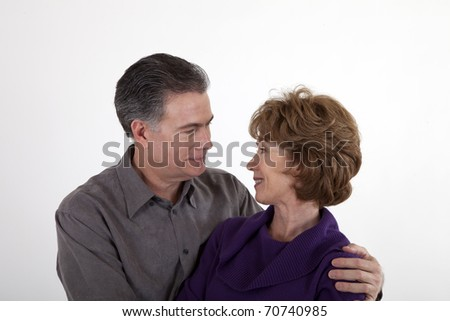 A smiling mature look lovingly into each others eyes.