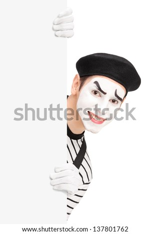 A smiling mime artist posing behind a blank panel, isolated on white background - stock photo