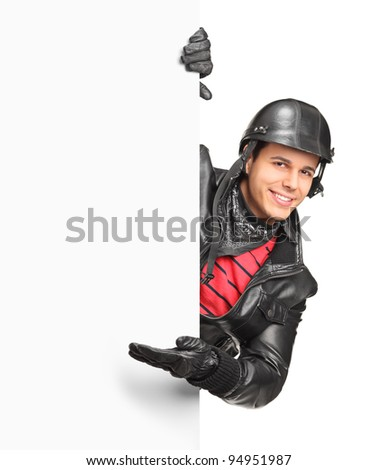 A smiling motorcycler gesturing welcome behind a white panel isolated on white background - stock photo