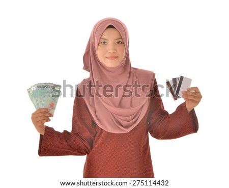 A smiling muslim woman holding a bunch of Malaysian Ringgit and credit cards, isolated on white background.