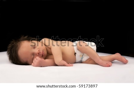 A smiling newborn infant sleeping on a white and black background - stock photo