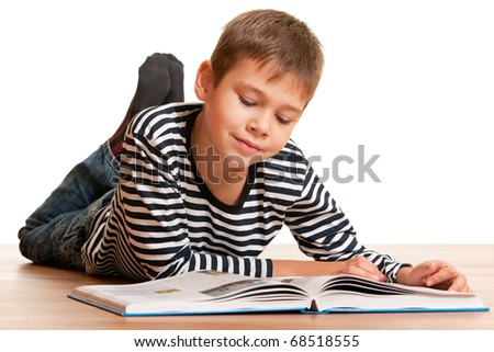 A smiling reading boy lying on the wooden floor; isolated on the white background