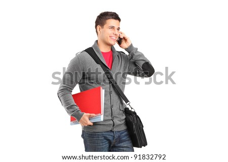 A smiling school boy holding books and talking on a phone isolated on white background - stock photo