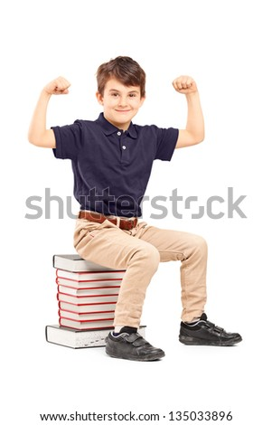 A smiling schoolboy showing his muscles seated on a pile of books, isolated on white background - stock photo