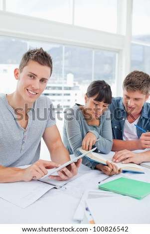 A smiling student using a tablet looks into the camera as his friends use a book to find the answer - stock photo