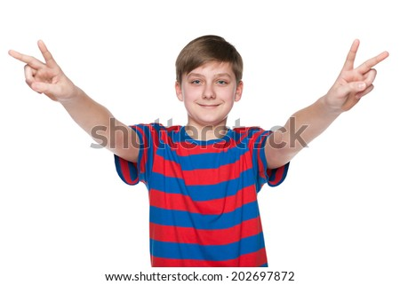 A smiling teen boy shows victory signs against the white background - stock photo