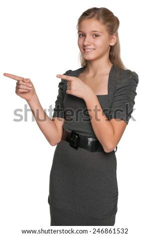 A smiling teen girl shows her fingers to the side against the white background - stock photo