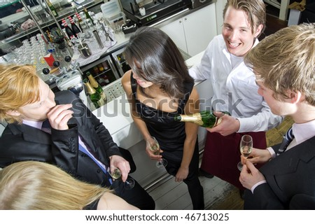 A smiling waiter, looking at the camera, whilst refilling his guest's glasses - stock photo