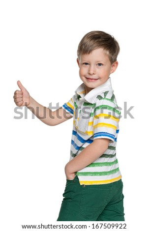 A smiling walking boy holds his thumb up on the white background - stock photo
