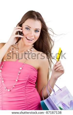 A smiling woman holding a credit card and talking on the mobile phone, isolated on white background