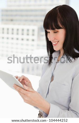 A smiling woman in her office using her tablet pc - stock photo