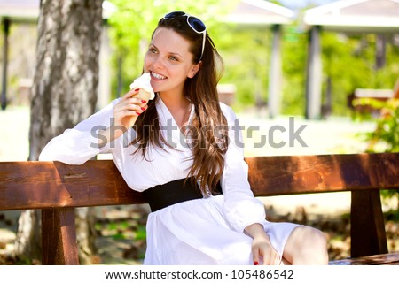 A smiling woman is eating an ice cream in the park - stock photo