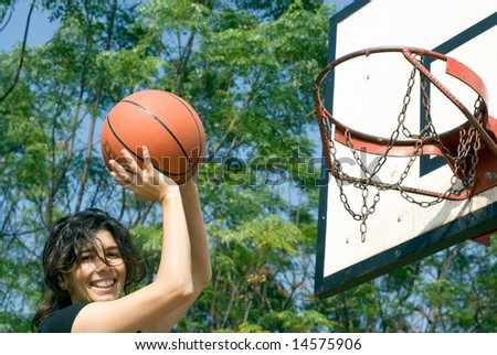 A smiling woman is playing basketball on a court at the park.  The woman is looking at the camera and about to make a shot.  Horizontally framed photo. - stock photo