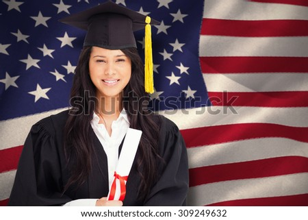 A smiling woman looking at the camera while dressed in her graduation gown against united states of america flag