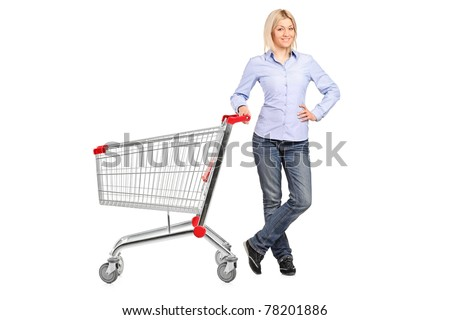 A smiling woman posing next to an empty shopping cart isolated on white background - stock photo