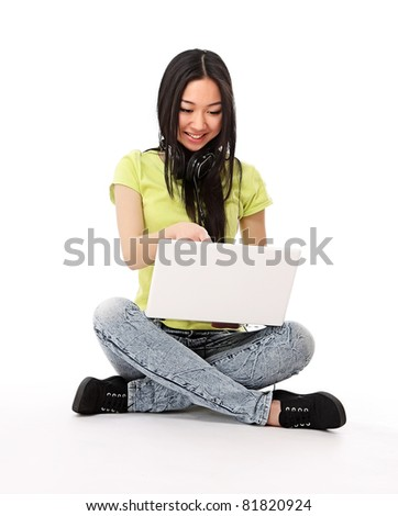 A smiling woman sitting on a floor with a laptop and headset, isolated on white - stock photo