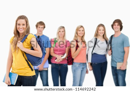 A smiling woman standing in front of her friends as they all look into the camera - stock photo