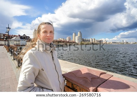 A smiling woman stands close to the river, her hair is moved by the wind under a dramatic stormy spring sky - stock photo