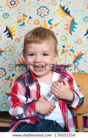 A smiling young boy sitting on a chair. - stock photo