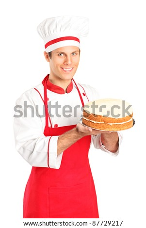 A smiling young chef holding a cake isolated on white background - stock photo